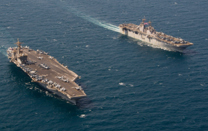 ARABIAN GULF (Aug. 28, 2015) The Wasp-class amphibious assault ship USS Essex (LHD 2) transits alongside the aircraft carrier USS Theodore Roosevelt (CVN 71). Theodore Roosevelt is deployed in the U.S. 5th Fleet area of operations supporting Operation Inherent Resolve, strike operations in Iraq and Syria as directed, maritime security operations and theater security cooperation efforts in the region. (U.S. Navy photo by Mass Communication Specialist 2nd Class Chris Brown/Released)